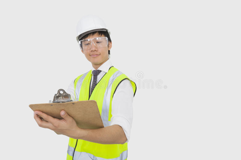 Confident construction worker holding clipboard in office royalty free stock photo