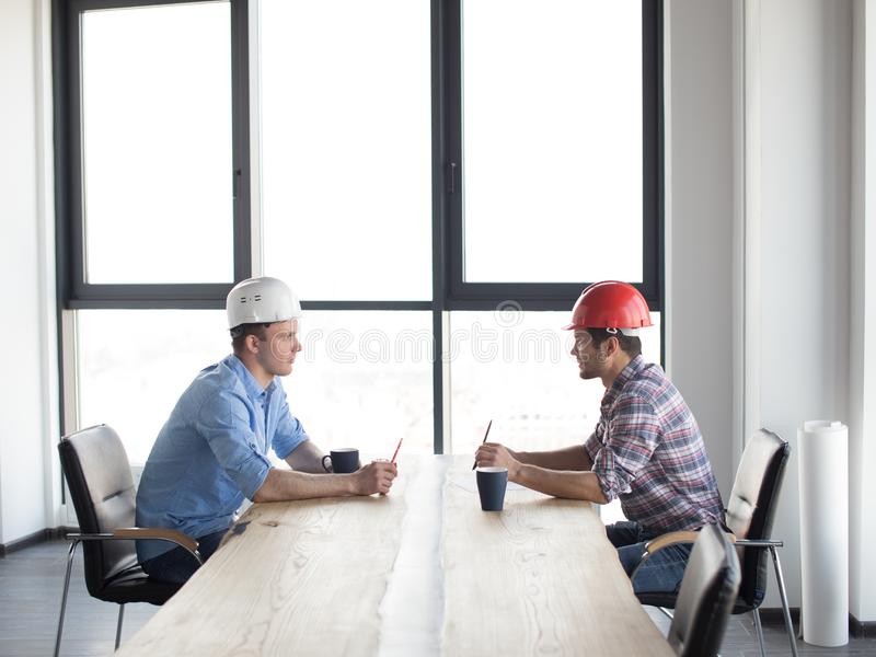Confident constructors are solving problems while sitting at the table stock photo