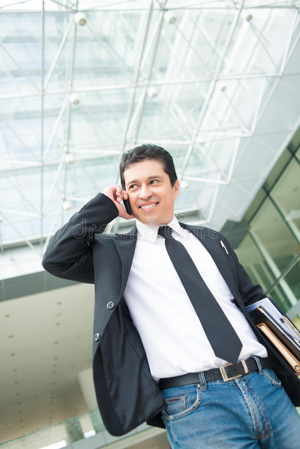 Confident conversation. Smiling businessman talking by phone indoors royalty free stock image