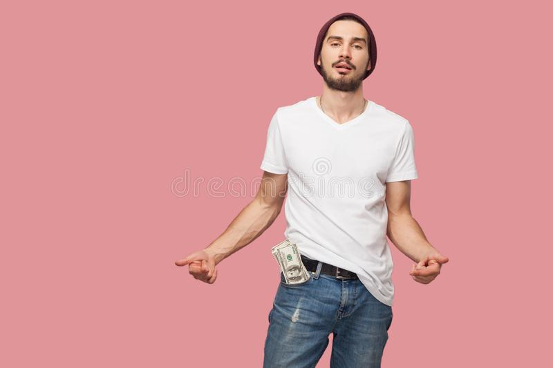 Confident cool handsome bearded young hipster man in white shirt and casual hat standing, hold money on the pocket, and pointing stock images
