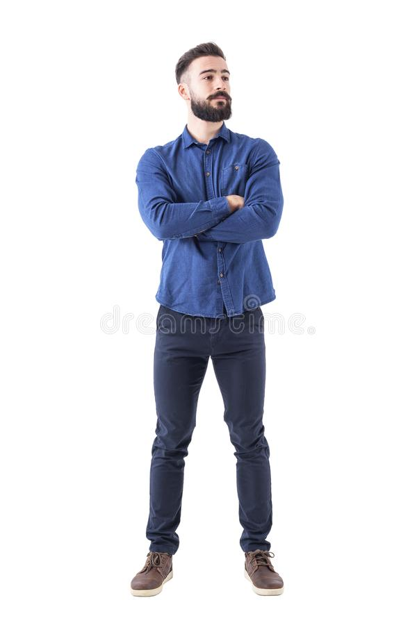 Confident cool young bearded man standing and looking away with crossed hands royalty free stock photos
