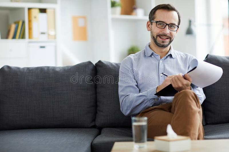 Confident counselor. Successful cheerful psychologist with document making notes while sitting on couch in front of camera royalty free stock image