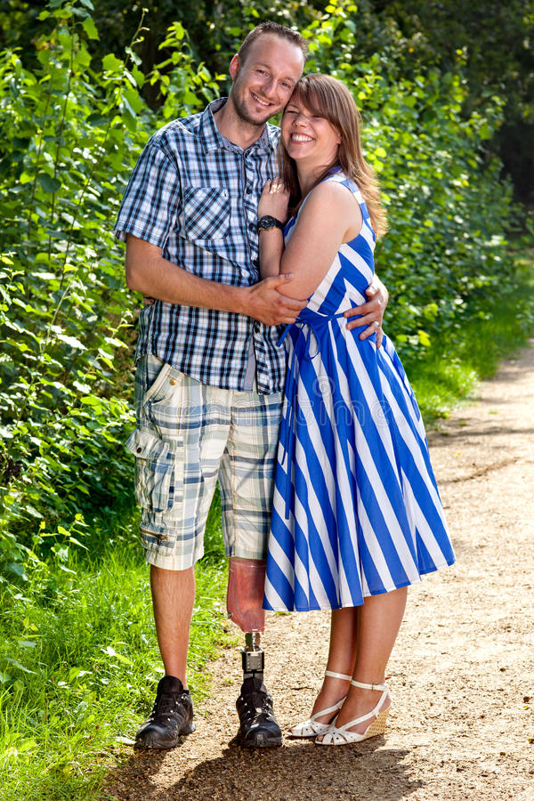 Confident couple in a loving embrace. Confident attractive smiling young couple in a loving embrace standing outdoors on a gravel path - the men is a handicapped royalty free stock photos