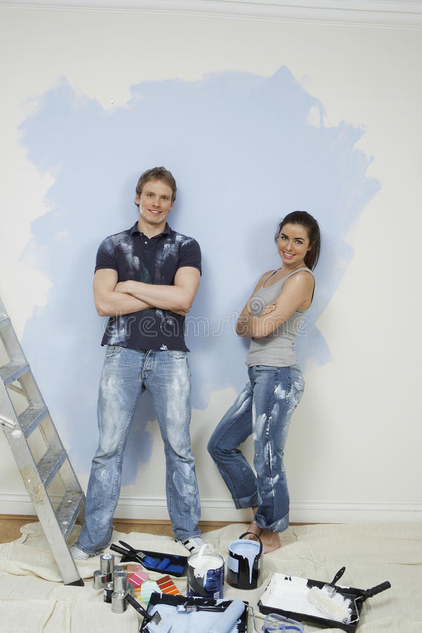 Confident Couple Standing Against Wall With Painting Tools In Foreground royalty free stock images
