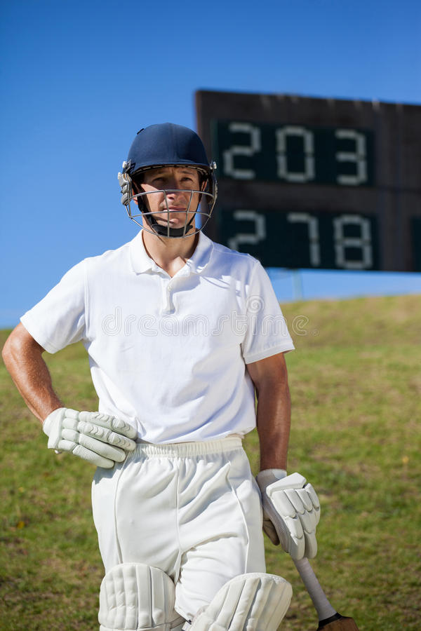 Confident cricket player with bat at field. Confident cricket player with bat standing against scoreboard at field stock images