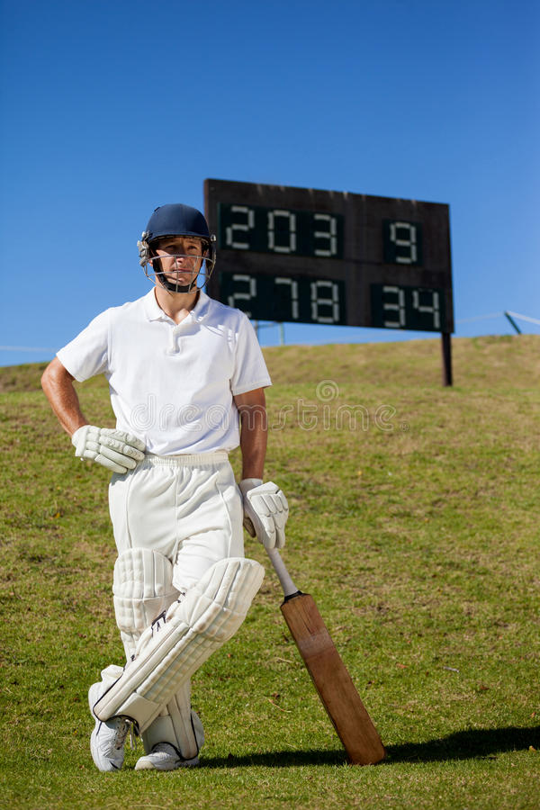Confident cricket player with bat standing against scoreboard. Full length of confident cricket player with bat standing against scoreboard on field stock image