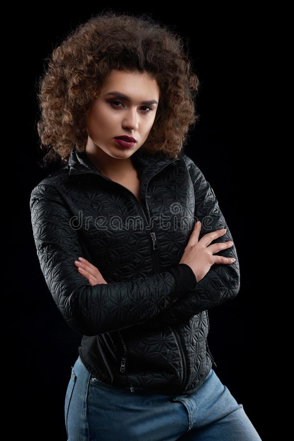 Confident curly girl wearing black jacket and blue jeans. royalty free stock image