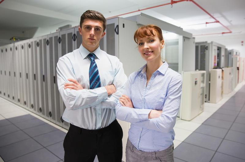 Confident data technicians looking at camera. In large data center royalty free stock photos
