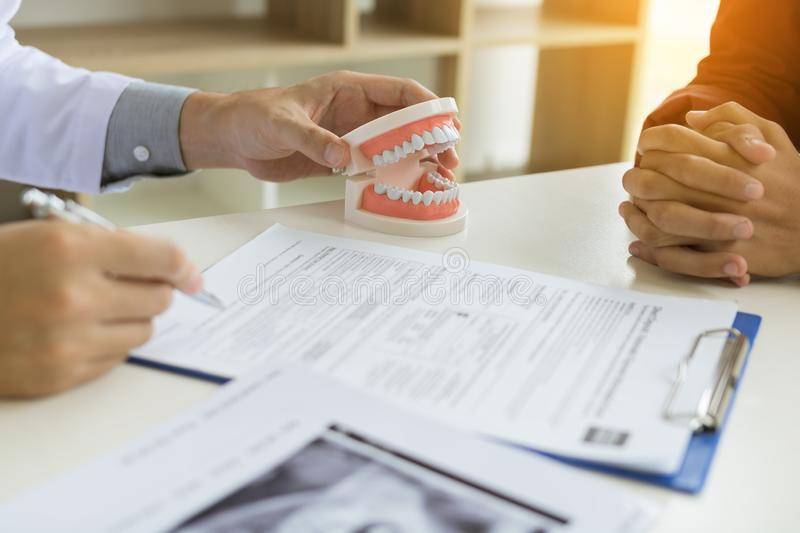 Confident dentist man holding a dentures with talking senior patient at office room stock photography