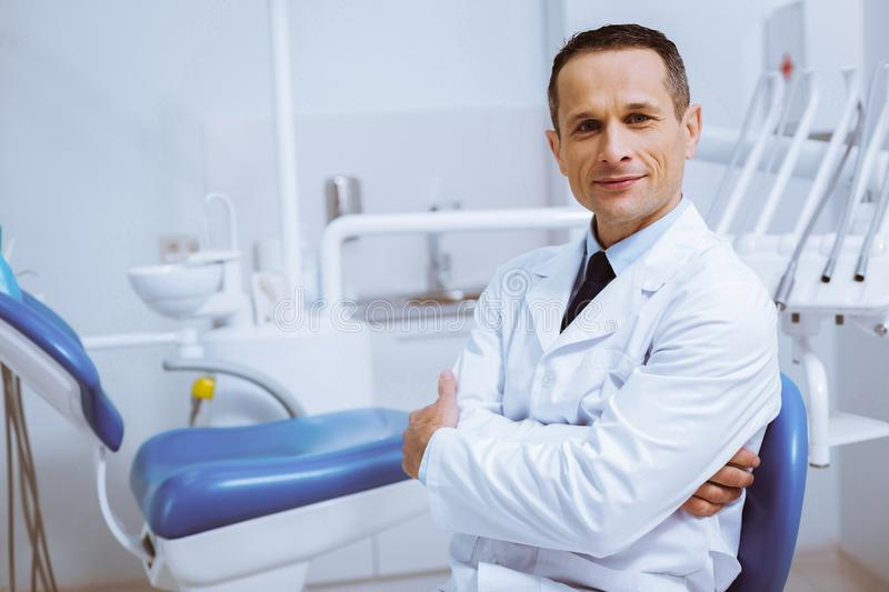 Confident dentist sitting in his cabinet. Ready to work. Delighted male person wearing medical uniform while being at workplace royalty free stock images