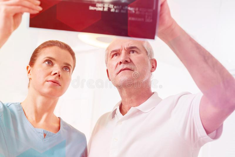 Confident dentists analyzing x-ray at dental clinic royalty free stock photo