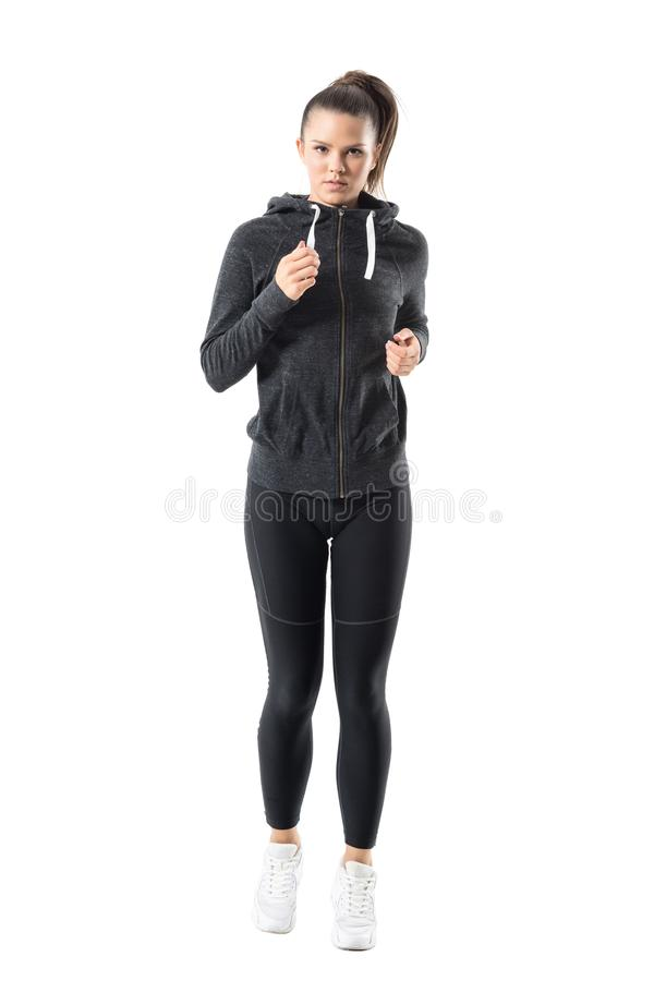 Confident determined young woman jogger in hooded sweatshirt jogging and looking at camera. stock image