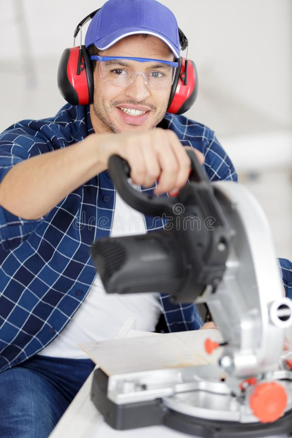 Confident diligent friendly workman ready to working on circular saw stock photo