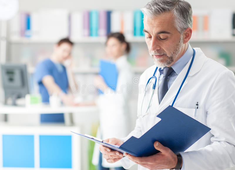 Confident doctor checking medical records stock image