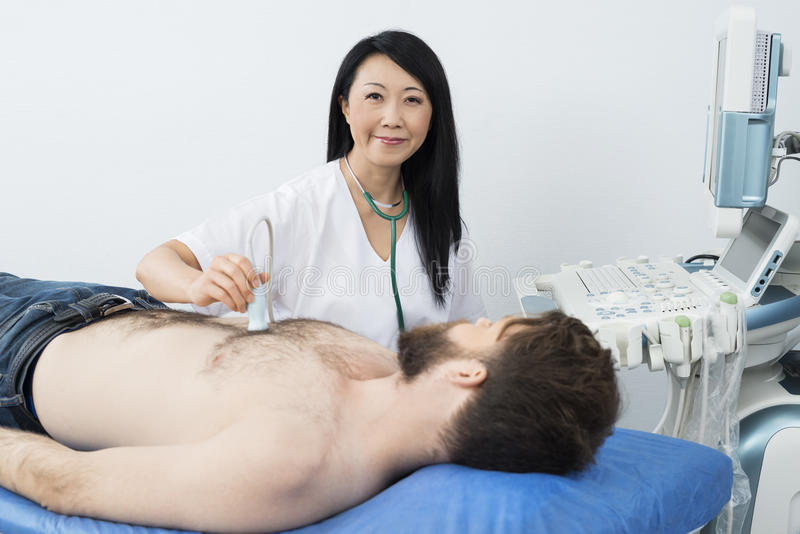 Confident Doctor Performing Ultrasound Test On Patient. Portrait of confident female doctor performing ultrasound test on male patient in hospital stock photos