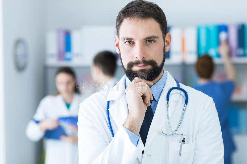 Confident doctor posing in the office stock image