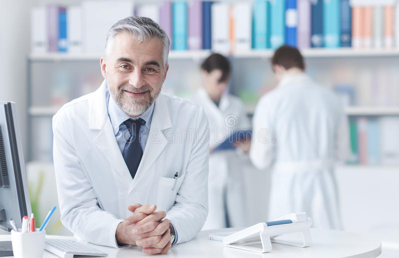 Confident doctor at the reception desk stock photos