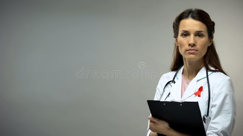 Confident doctor with red ribbon looking into camera, anti-AIDS campaign concept royalty free stock photography