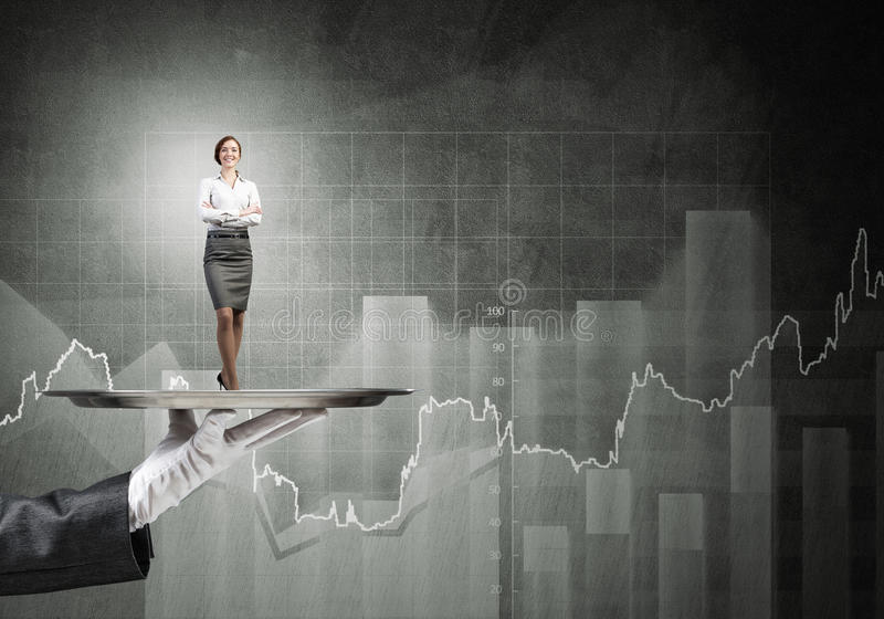Confident elegant businesswoman presented on metal tray and graphs at background. Miniature of businesswoman standing on tray held by hand royalty free stock photo