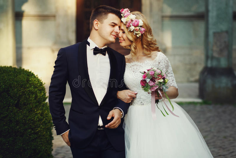 Confident elegant groom and beautiful shy bride holding hands outdoors closeup royalty free stock images
