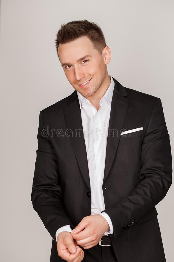 A confident elegant handsome young man standing in front of a grey background in a studio wearing a nice suit stock images