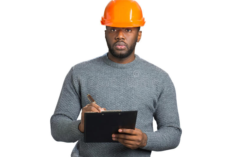Confident engineer writing on clipboard. royalty free stock images
