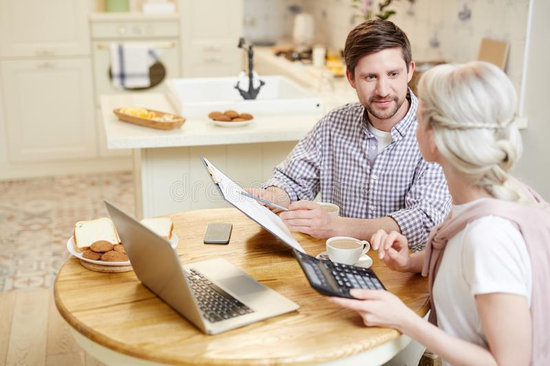 Couple filing tax return. Confident enterprising young couple filing tax return and discussing document while checking financial figures and drinking coffee in stock image
