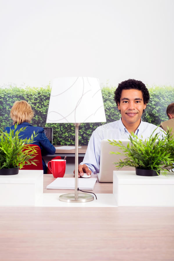 Confident Environmentalist In Office. Portrait of confident environmentalist sitting at desk in office royalty free stock photography
