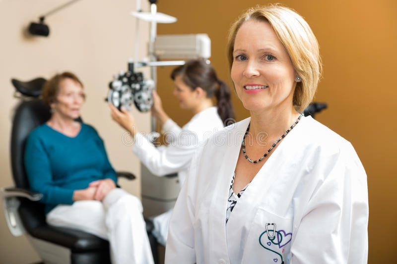 Confident Eye Doctor With Colleague Examining. Portrait of confident eye doctor with colleague examining patient in background royalty free stock images