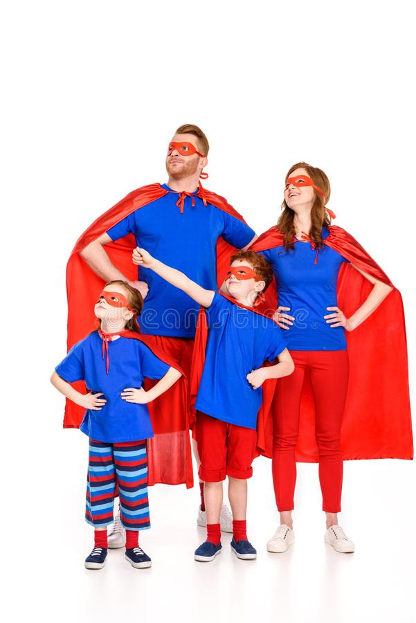 confident family of superheroes in masks and cloaks standing with hands on waist and looking away stock images