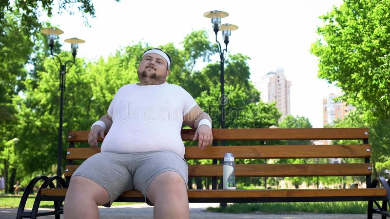 Confident fat man sitting in park, feels happy, contented with life, self-love royalty free stock photo