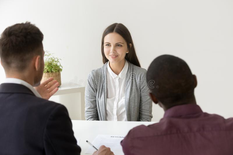 Confident applicant smiling at job interview with diverse hr man. Confident female applicant smiling at job interview with diverse hr managers, young happy stock image