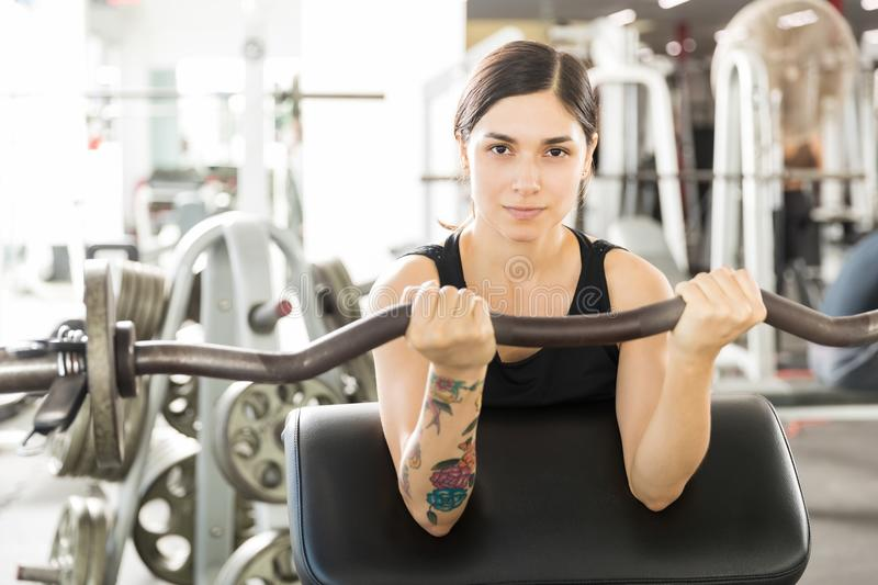 Confident Female Athlete Lifting Barbell Curl On Exercise Machine. Portrait of confident female athlete lifting barbell curl on exercise machine in gym royalty free stock images