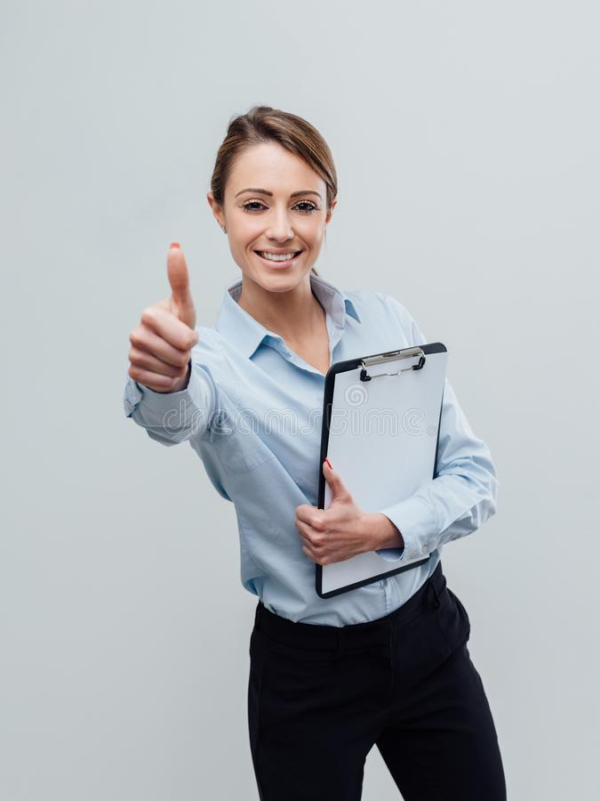 Confident female business executive giving a thumbs up stock image