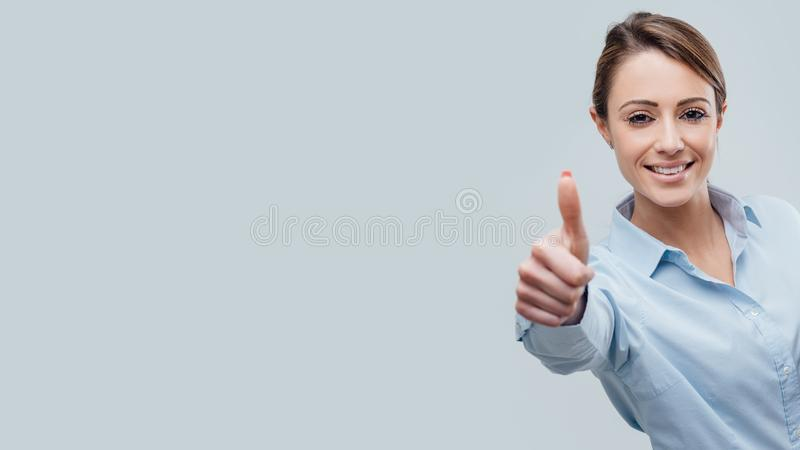 Confident female business executive giving a thumbs up royalty free stock image
