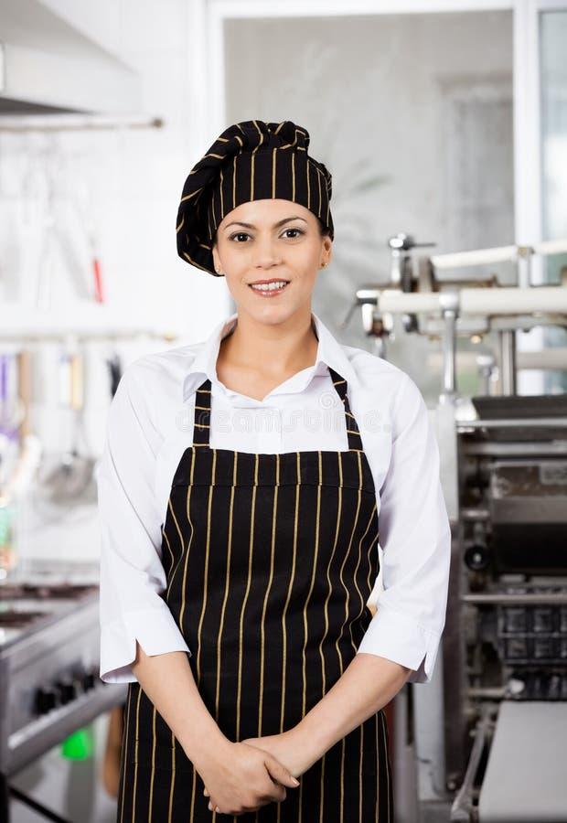 Confident Female Chef Standing In Kitchen stock photo