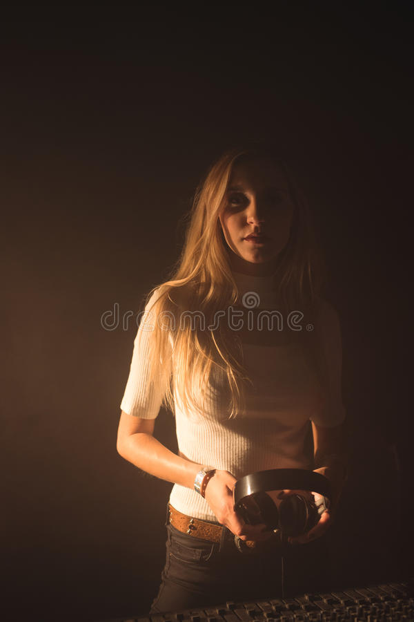 Confident female DJ holding headphones while standing by sound mixer in nightclub royalty free stock photo