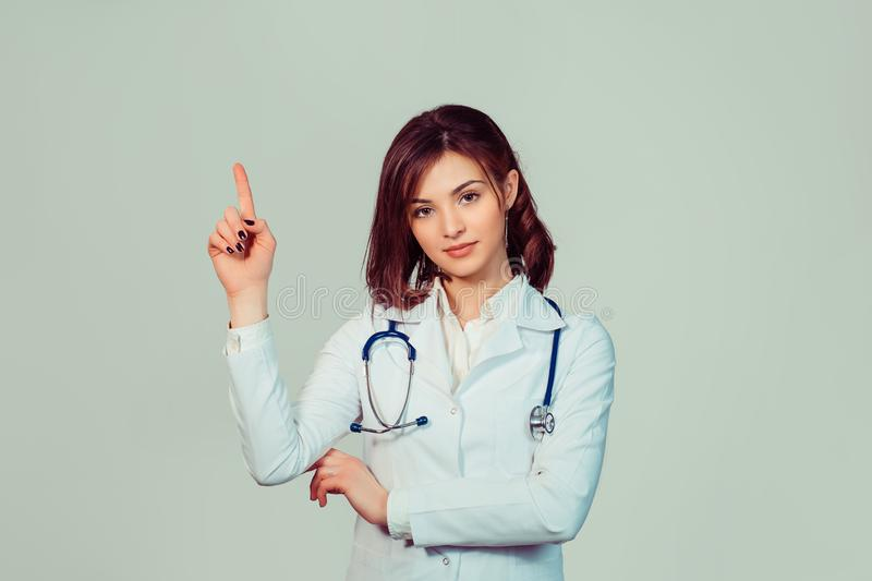 Confident female doctor. Cheerful healthcare professional pointing away stock photo