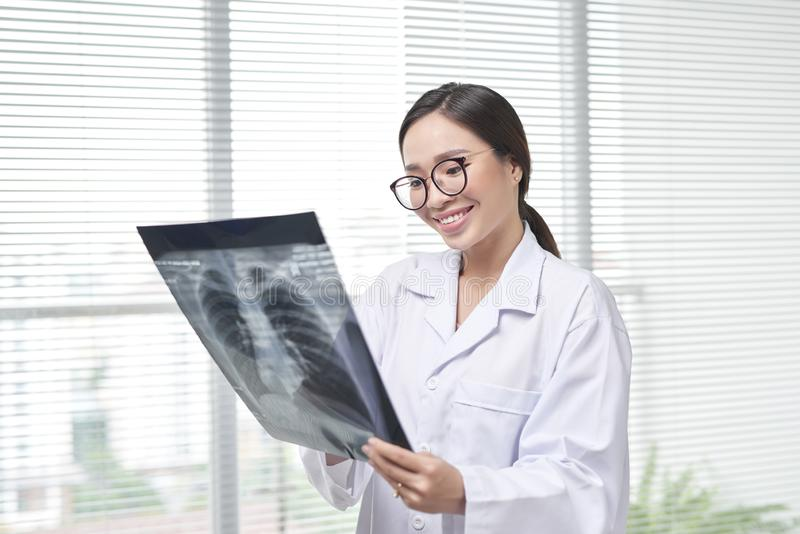 Confident female doctor examining accurately a rib cage x-ray.  stock photo