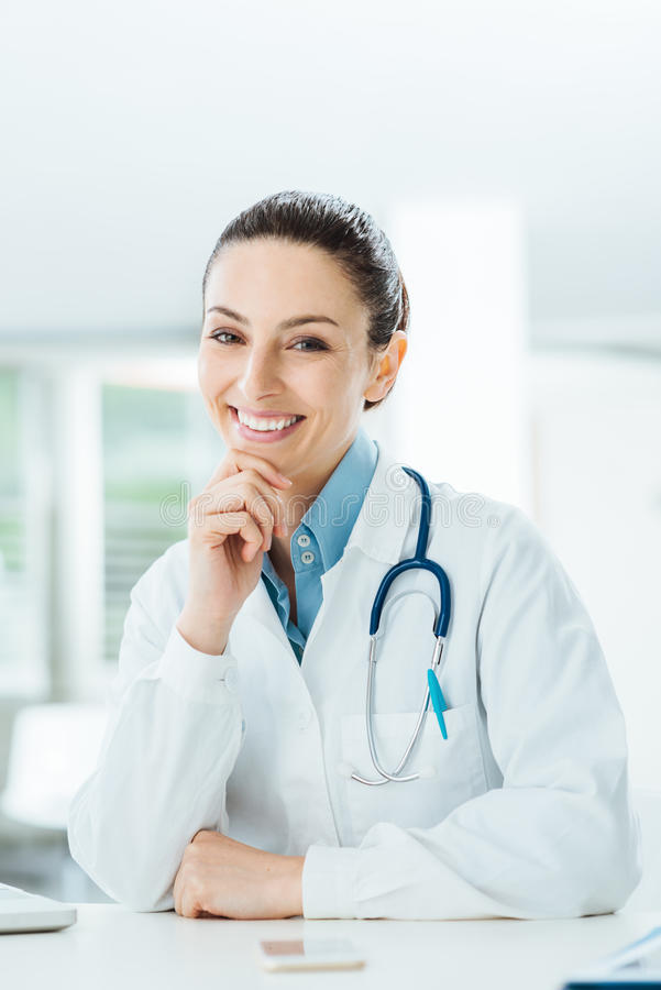Confident female doctor at office desk stock image