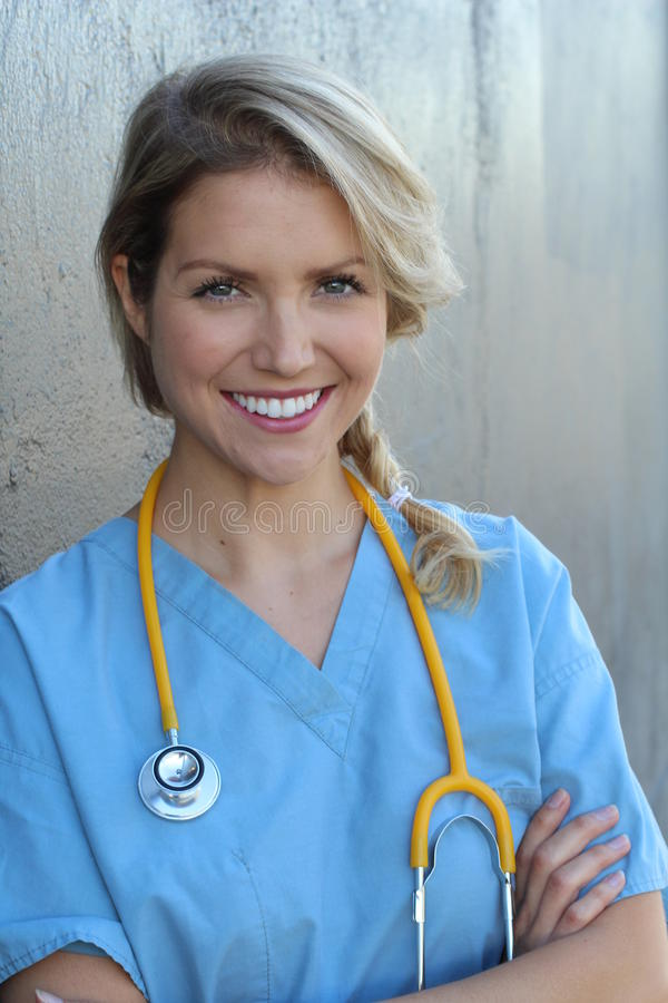 Confident female doctor posing in her office and smiling at camera, health care and prevention concept royalty free stock photo