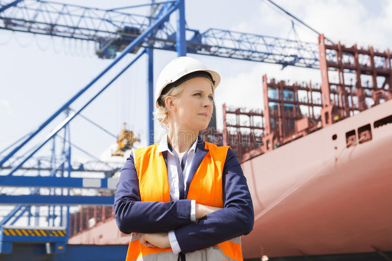 Confident female engineer in shipping yard stock image