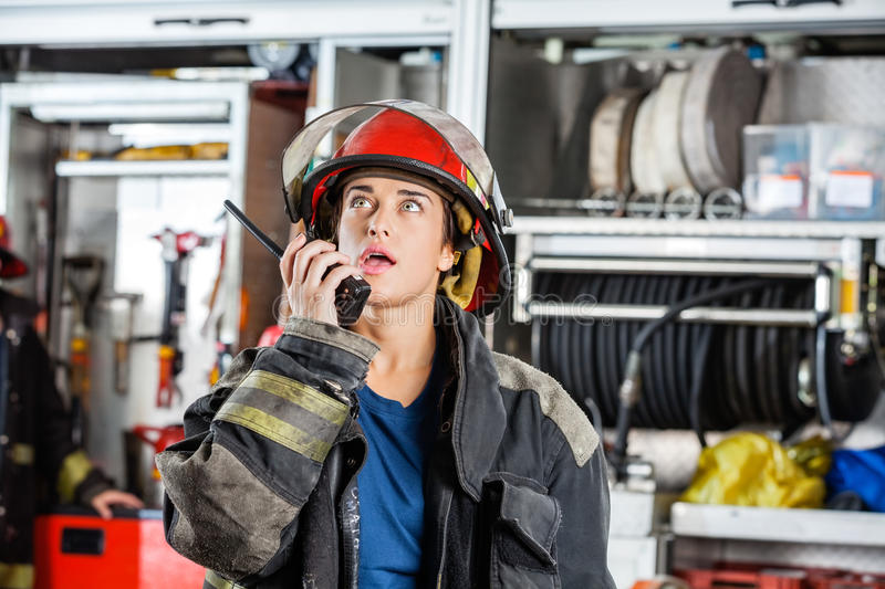 Confident Female Firefighter Using Walkie Talkie. Confident female firefighter looking up while using walkie talkie at fire station royalty free stock photo