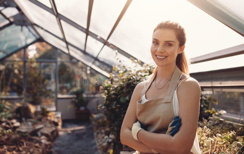 Confident female gardener at plant nursery stock image