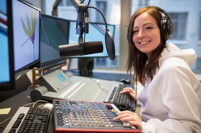 Confident Female Host Smiling In Radio Station. Portrait of confident female host smiling while using music mixer in radio station stock photography
