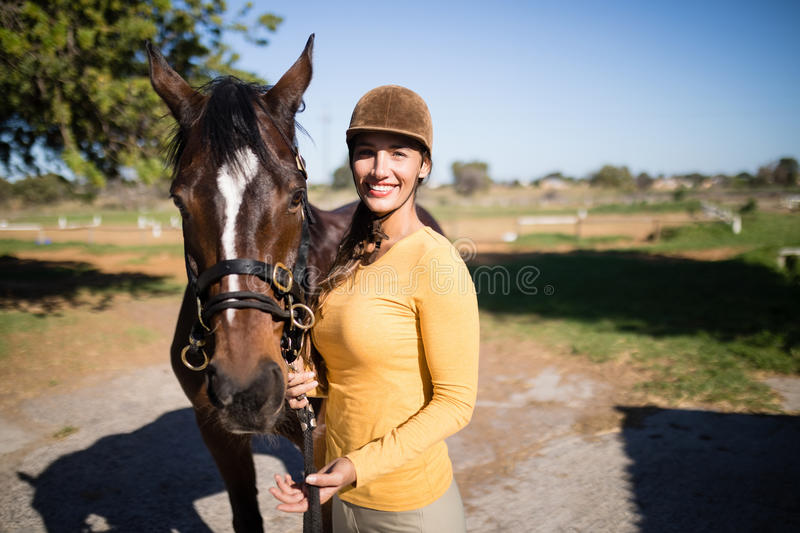 Confident female jockey with horse standing on field. Portrait of confident female jockey with horse standing on field royalty free stock images