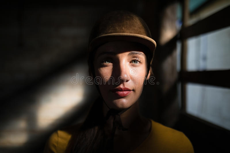 Confident female jockey in stable. Portrait of confident female jockey in stable royalty free stock image