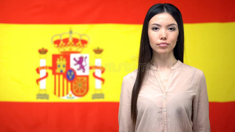 Confident female looking at camera, Spanish flag background, passport control stock image