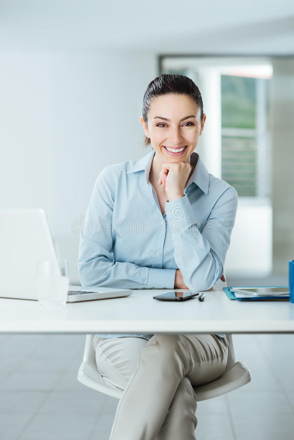 Confident female manager at desk posing stock image