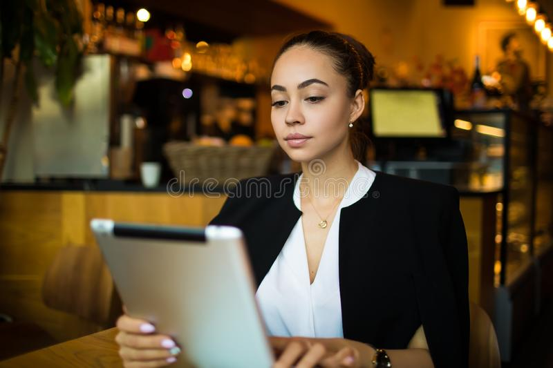 Confident female manager reading financial news via digital tablet. Online banking stock photography